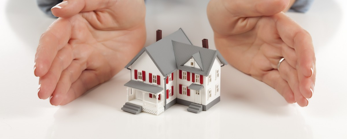 Womans Hands Around Model House on White Surface.